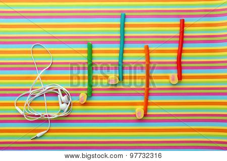 Treble clef with musical notes of candies and headphones on striped background