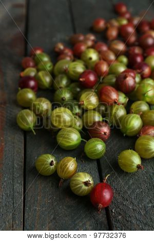 Red and green gooseberry on wooden table close-up