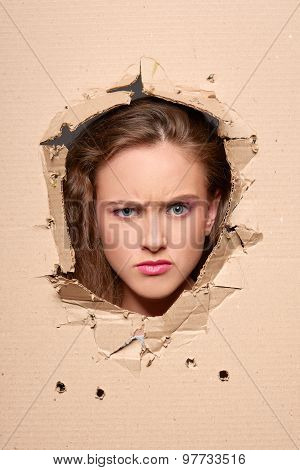 Displeased girl peeping through hole in paper