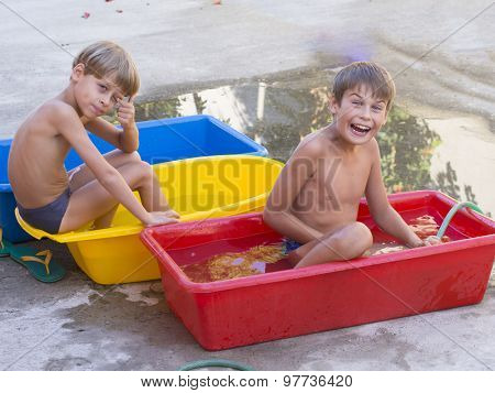 boys bathing in small tubs outdoor
