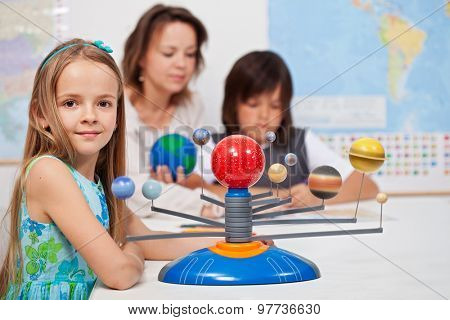 Kids study the solar system under their teacher supervision - focus on the little girl in front