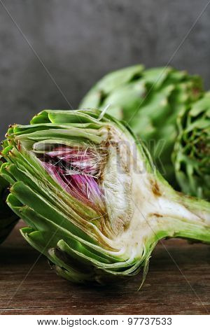 Artichokes on cutting board, on color wooden background