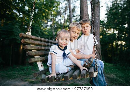 three brothers sitting on swing