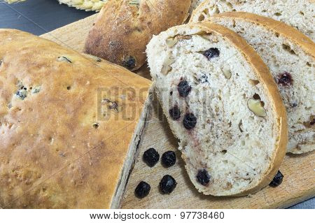 Fruit Bread With Aronia Sliced On A Wooden Plate With Dried Aronia Decoration
