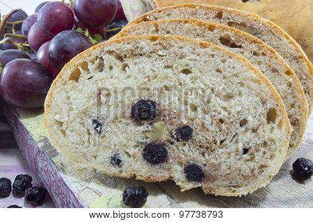 Fruit Bread With Aronia Sliced On A Wooden Plate With Dried Aronia And Fresh Grape Decoration