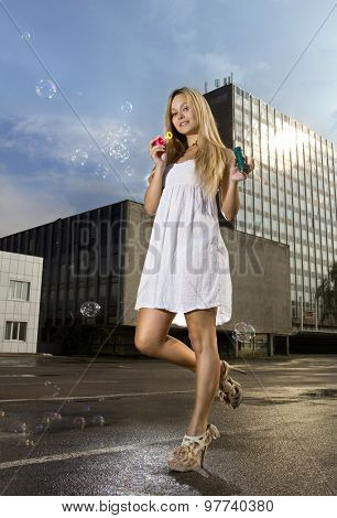 young blonde woman blowing soap bubbles on a street of city