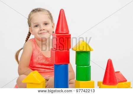 The Four-year Girl Sits At A House Out Of Blocks