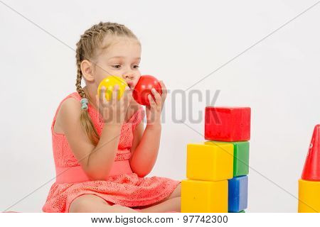 Child Being Played In Developing A Set Of Put Two Balls To The Cheeks