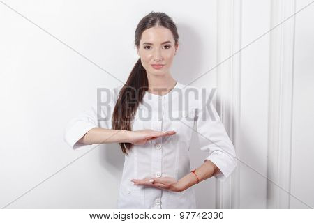 Young doctor with holding pose on white clinic background