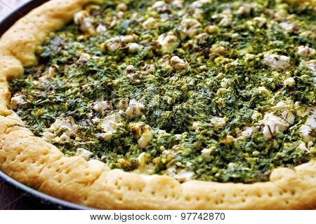 Open pie with spinach close up