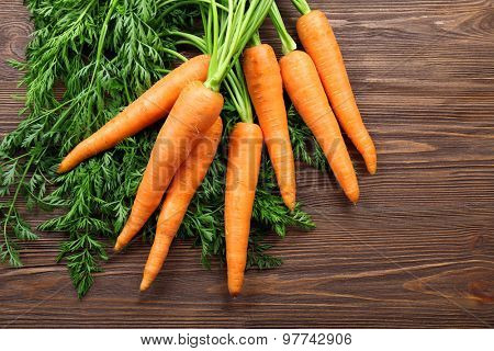 Fresh organic carrots with green tops on wooden background