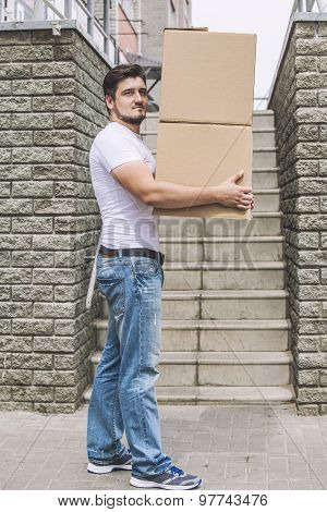 Porter, The Man With Cardboard Boxes In The Hands Of A Strong, Delivery To The Door
