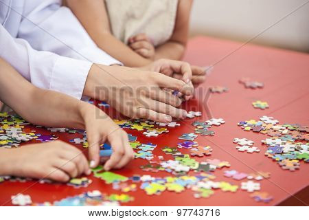 Children, Friends Hands Assemble The Puzzle On The Table Color