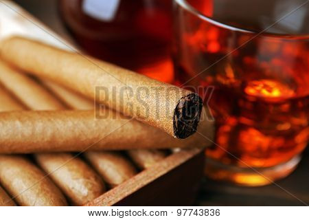 Cigars with glass of cognac on wooden table, closeup