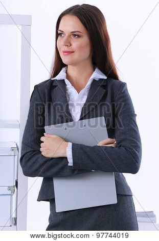 Young business woman standing in office.