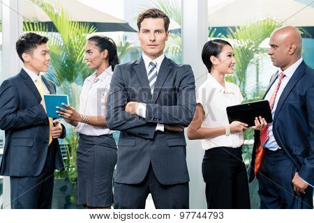 Business team meeting with man in front looking at camera, in the background people of diverse ethnicities discussing