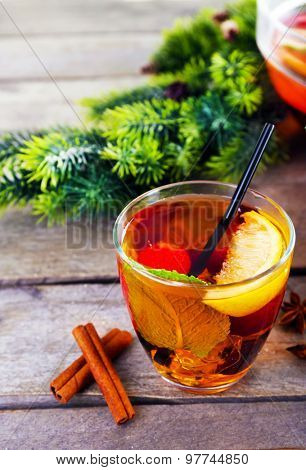 Sangria in glass with Christmas decoration on wooden table close up