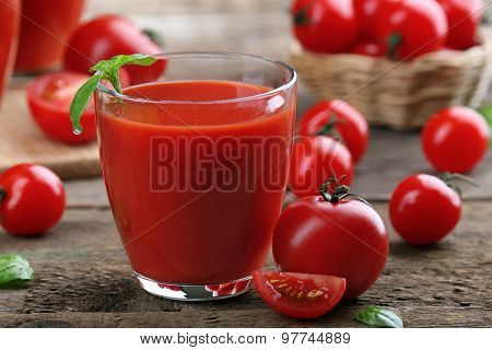 Glass of tomato juice on wooden table, closeup