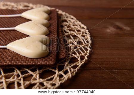 Chocolate heart shaped candies on sticks on brown napkin, closeup