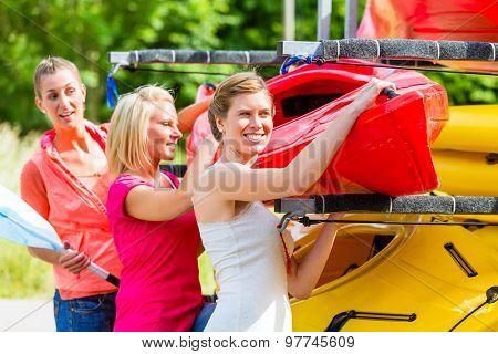 Three women unloading kayak from boat trailer
