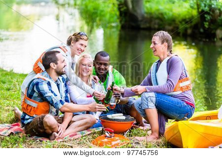 Friends barbecue after sports in forest drinking beer, kayaks sitting in front of river