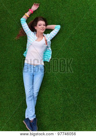 Top view of beautiful young woman holding hands behind head.