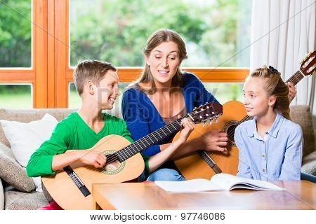 Family making music at home with guitar, mother, daughter and son playing