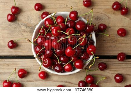 Sweet cherries in bowl on wooden table close up