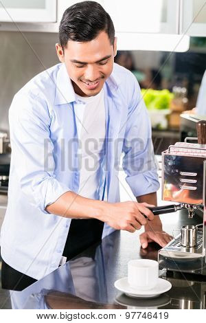 Asian man making espresso coffee in his kitchen