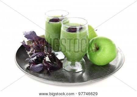 Glasses of green healthy juice with basil and apple isolated on white