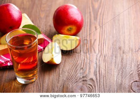 Glass of apple juice and fruits on table close up