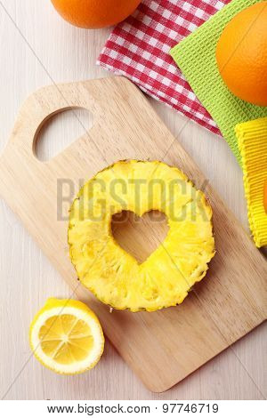 Pineapple slice with cut in shape of heart on table close up