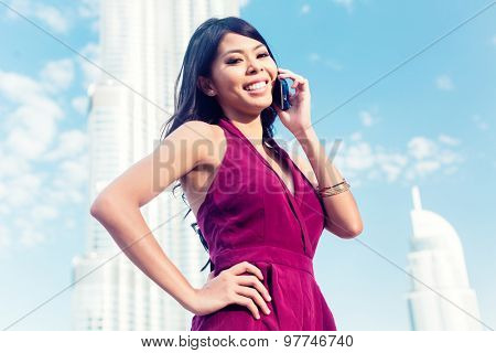 Tourist woman talking on phone in Dubai front of burj al khalifa