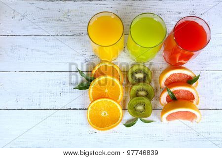Glasses of different juice with fruits and mint on wooden background