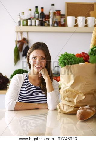 Young woman sitting in kitchen at home .