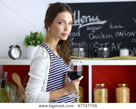 Pretty woman drinking some wine at home in kitchen .