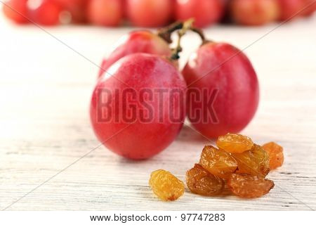 Raisins with grapes on table close up