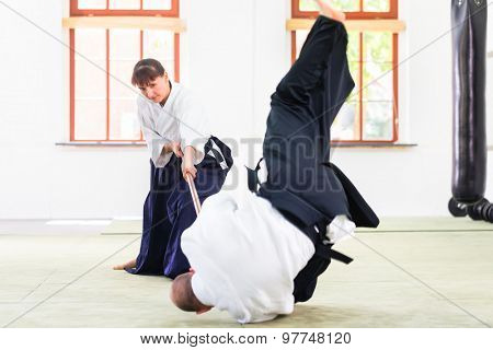 Man and woman fighting with wooden stick at Aikido training in martial arts school