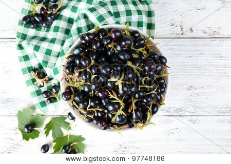 Ripe black currants in bowl on wooden table with checkered napkin, top view