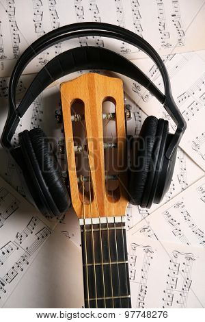Music recording scene with guitar and headphones on music sheets background