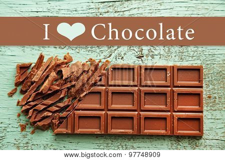 Chopped bar of chocolate on color wooden surface and space for text