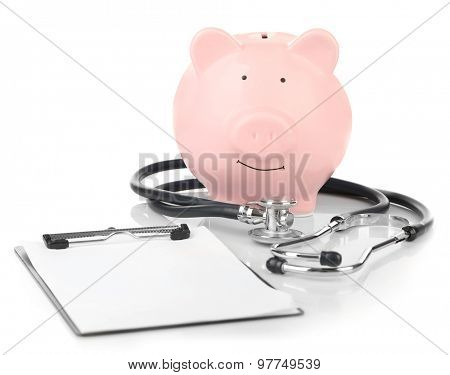 Piggy bank with stethoscope and clipboard isolated on white