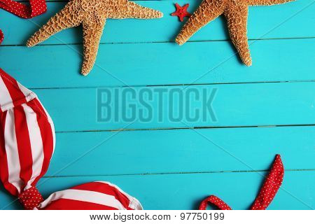 Swimsuit and starfishes on green wooden background