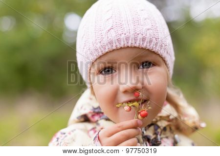child holding hand wild strawberry twig and eating fun