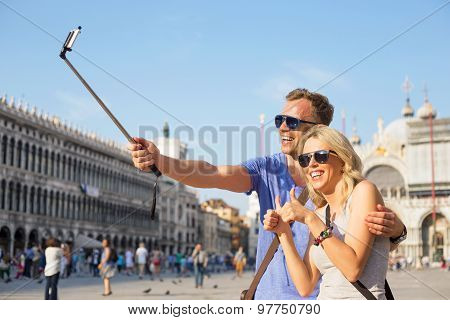 Tourists using selfie stick to make photo with smartphone