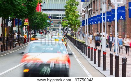 Downtown of Fukuoka city during peak time. Taxi cars aligned on the street.