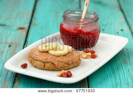 Breakfast Of Homemade Cookie With Peanut Butter, Banana And Raspberry Jam In Small Jar On White Dish