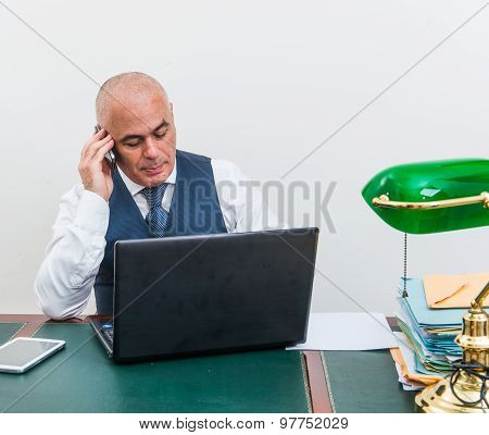 A Business Man On The Phone And Pc, At Desk, In Conference Call And Bald.