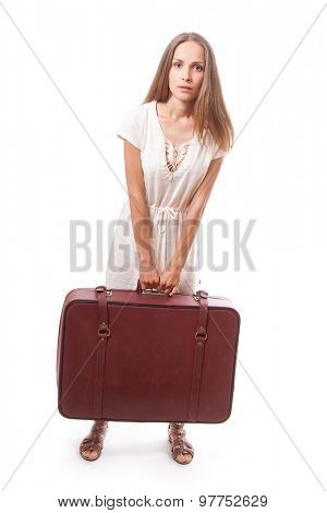 Girl standing with suitcase. Isolated over white background.