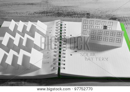 Handmade model of solar panels in notebook on wooden table, closeup